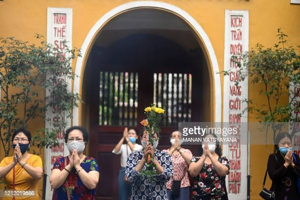 Devotees wearing face masks as a preventive measure against the spread of the COVID-19 coronavirus offer prayers at Quan Su pagoda in Hanoi on May 7...