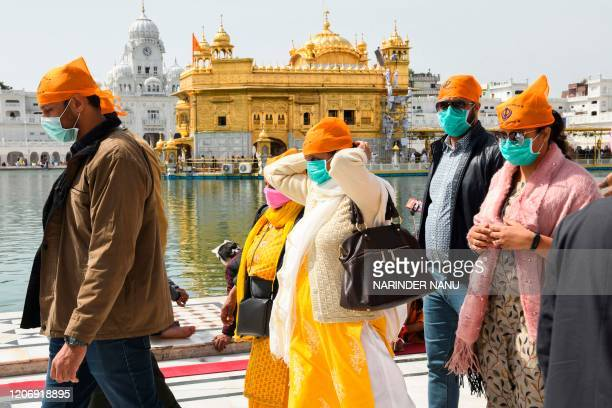 Devotees, wearing facemasks amid concerns over the spread of the COVID-19 novel coronavirus, arrive to pray at the Golden Temple in Amritsar on March...