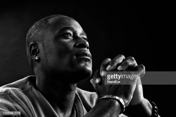 devout african or african american man prays, hands clasped - religion stock pictures, royalty-free photos & images