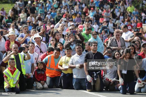 Devout Catholics kneel in prayer during a traditional Via Crucis or Way of the Cross procession on the Christian Good Friday holiday at St Camillus...