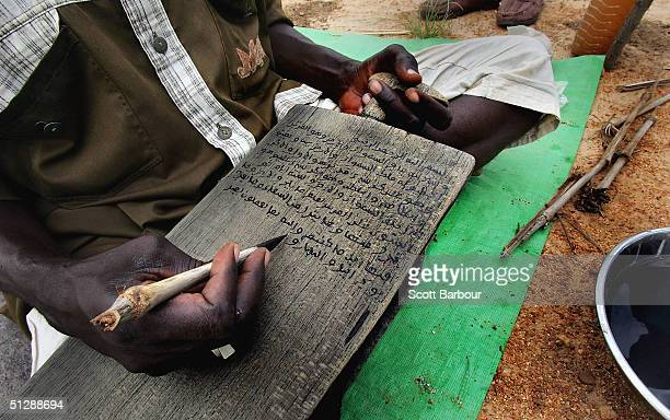 A devout Muslim rebel from the Sudanese Justice and Equality Movement passes time writing koranic verses on a wood block at their base in the Darfur...