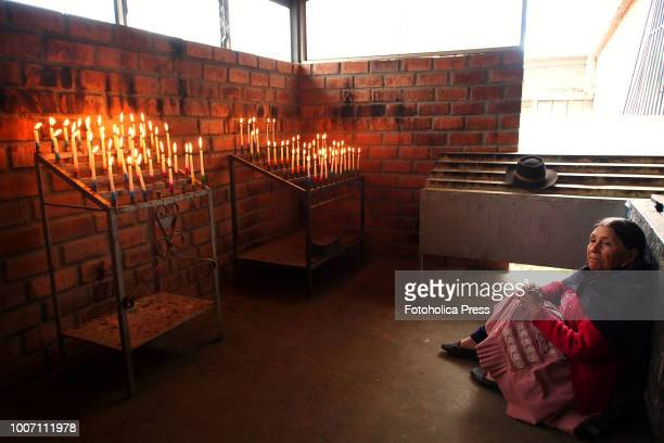 SAPALLANGA HUANCAYO JUNIN PERU A devout old woman sitting on the floor praying in front of burning candles for the Virgin of Cocharcas in the church...