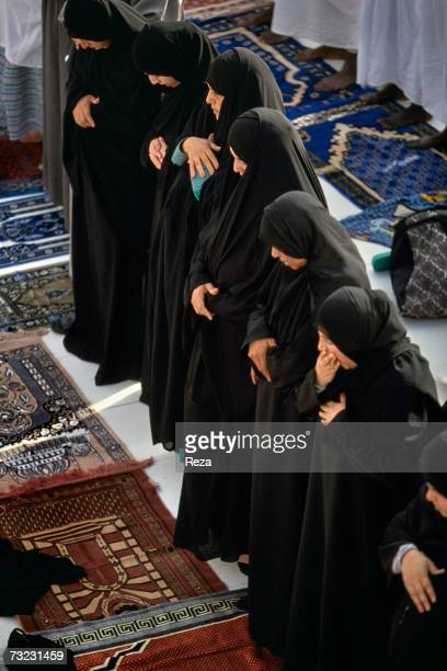 Devout women stand during Asr prayer in front of the Masjid AlHaram mosque on January 2003 in Mecca Saudi Arabia A long tunic and veil in private or...