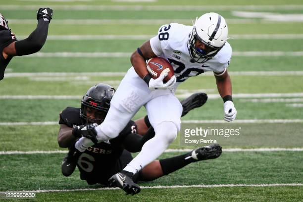 Devyn Ford of the Penn State Nittany Lions rushes for yards against Rashawn Battle of the Rutgers Scarlet Knights during the second quarter at SHI...