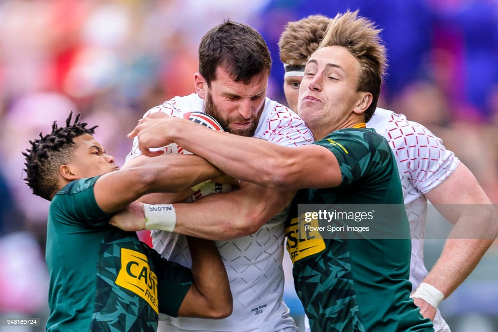 Dewald Human (L) and James Murphy of South Africa (R) puts a tackle on Charlie Hayter of England (C) during the HSBC Hong Kong Sevens 2018 match between South Africa and England on April 7, 2018 in Hong Kong, Hong Kong.