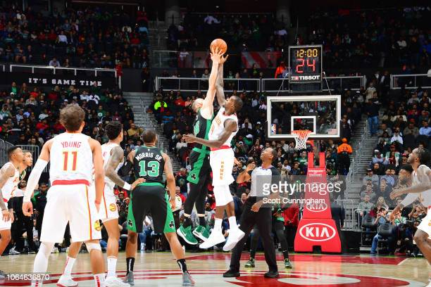 Dewayne Dedmon of the Atlanta Hawks and Aron Baynes of the Boston Celtics jump for tip off on November 23 2018 at State Farm Arena in Atlanta Georgia...