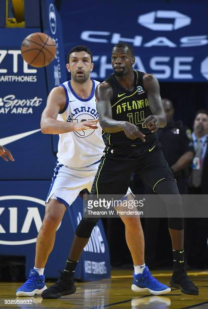 Dewayne Dedmon of the Atlanta Hawks passes the ball while guarded by Zaza Pachulia of the Golden State Warriors during an NBA basketball game at...