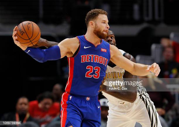 Dewayne Dedmon of the Atlanta Hawks reaches for a steal against Blake Griffin of the Detroit Pistons at State Farm Arena on November 9 2018 in...