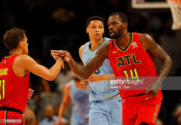 Dewayne Dedmon of the Atlanta Hawks reacts with Trae Young after they connected for a basket against the Memphis Grizzlies in the first half at State...