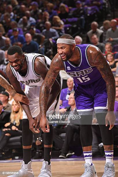 Dewayne Dedmon of the San Antonio Spurs and DeMarcus Cousins of the Sacramento Kings smile and laugh while waiting for a rebound on October 27 2016...