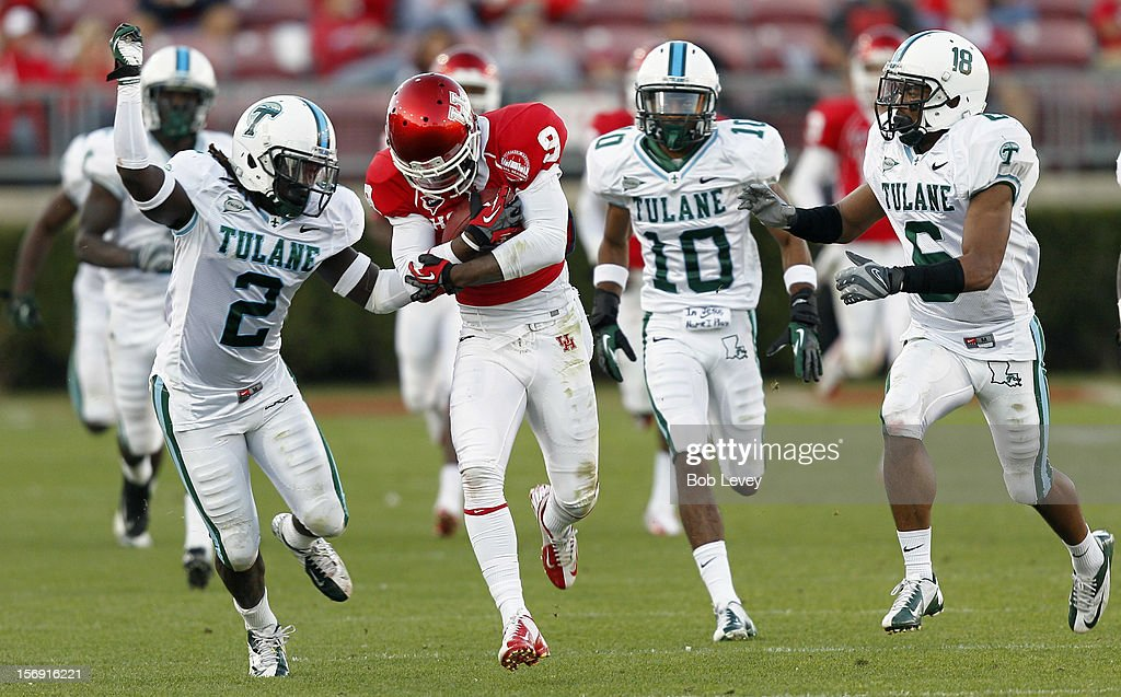 Dewayne Peace #9 of the Houston Cougars keeps the ball away from Darion Monroe #2 of the Tulane Green Wave at Robertson Stadium on November 24, 2012 in Houston, Texas. Houston defeats Tulane 40-17.