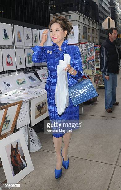 Dewi Sukarno is seen buying art work from a vendor on October 16 2010 inMadison AV New York