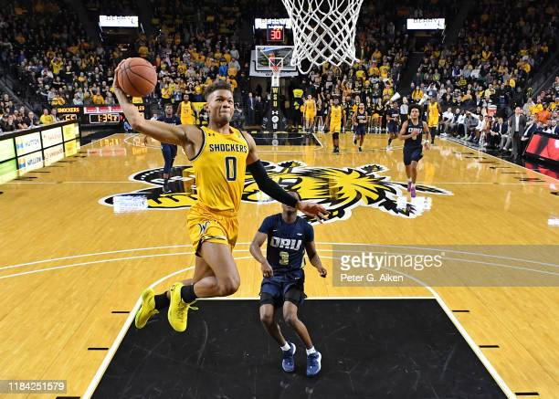 Dexter Dennis of the Wichita State Shockers drives to the basket for a dunk past Max Abmas of the Oral Roberts Golden Eagles during the second half...