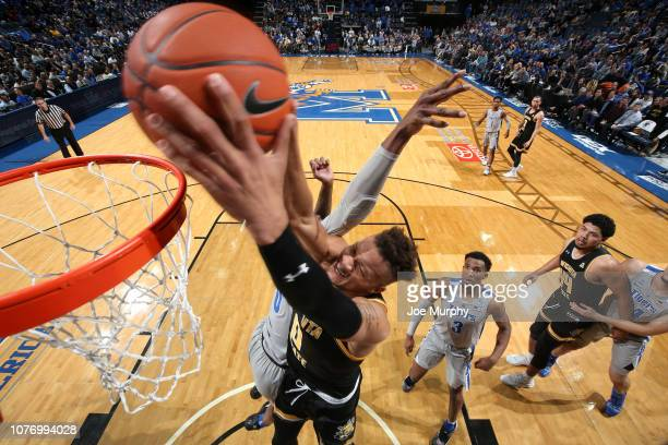 Dexter Dennis of the Wichita State Shockers dunks the ball against Kyvon Davenport of the Memphis Tigers on January 3 2019 at FedExForum in Memphis...