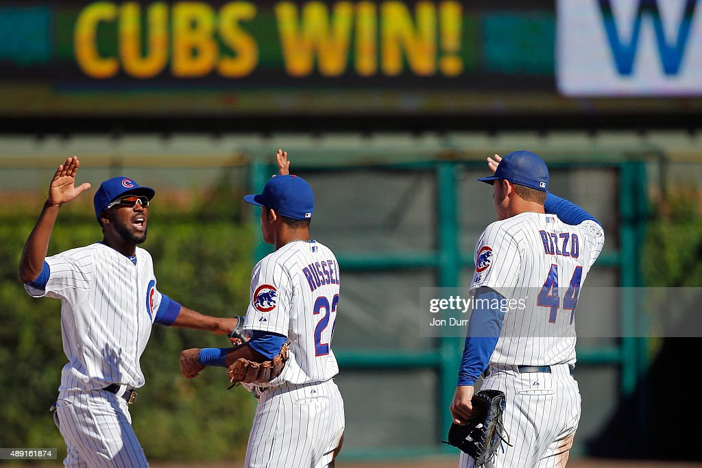 Dexter Fowler #24 of the Chicago Cubs (L), Addison Russell #22 and Anthony Rizzo #44 celebrate their win over the St. Louis Cardinals at Wrigley Field on September 19, 2015 in Chicago, Illinois. The Chicago Cubs won 5-4.