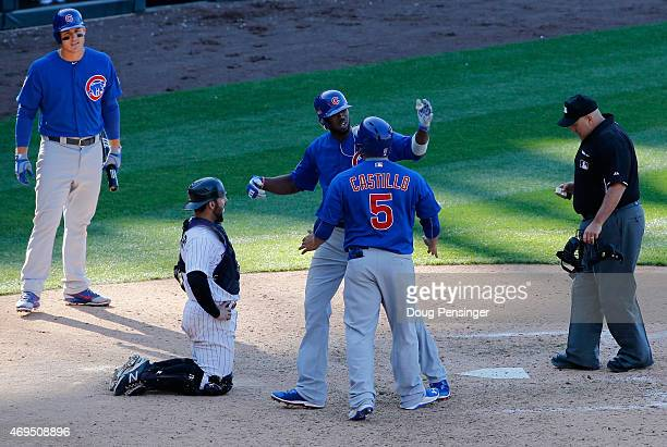 Dexter Fowler of the Chicago Cubs celebrates his game winning two run home run with Welington Castillo of the Chicago Cubs as catcher Michael McKenry...