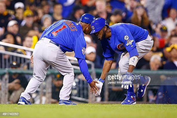 Dexter Fowler of the Chicago Cubs celebrates with Gary Jones of the Chicago Cubs after hitting a solo home run in the fifth inning during the...