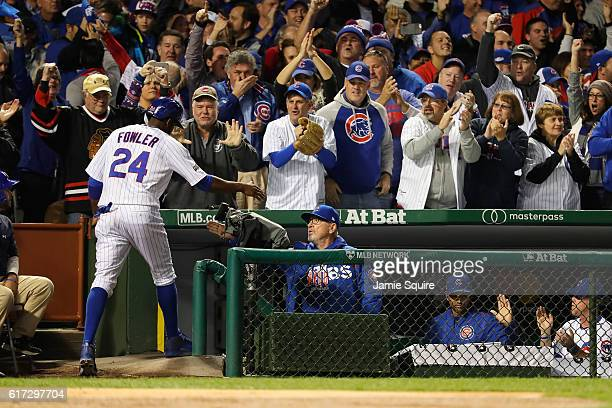 Dexter Fowler of the Chicago Cubs celebrates with manager Joe Maddon at the dugout after scoring a run on an RBI single hit by Kris Bryant in the...