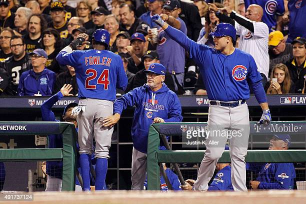 Dexter Fowler of the Chicago Cubs is congratulated by manager Joe Maddon of the Chicago Cubs after scoring a run on an RBI single by Kyle Schwarber...