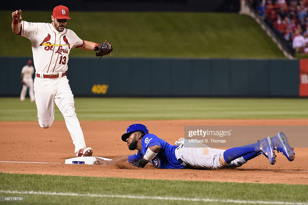 Dexter Fowler #24 of the Chicago Cubs is safe at third base as Matt Carpenter #13 of the St. Louis Cardinals attempts to force him out in the seventh inning during game two of the National League Division Series between the St. Louis Cardinals and the Chicago Cubs at Busch Stadium on October 10, 2015 in St Louis, Missouri.