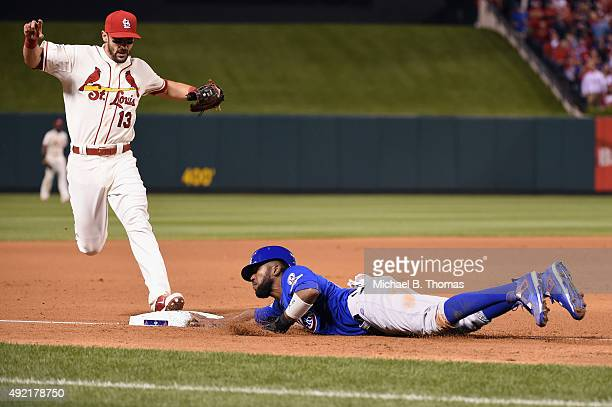 Dexter Fowler of the Chicago Cubs is safe at third base as Matt Carpenter of the St Louis Cardinals attempts to force him out in the seventh inning...