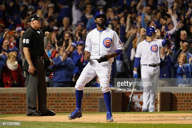 Dexter Fowler of the Chicago Cubs reacts after scoring a run on an RBI single hit by Kris Bryant in the first inning against the Los Angeles Dodgers...