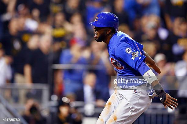 Dexter Fowler of the Chicago Cubs reacts at home plate after scoring a run on an RBI single by Kyle Schwarber of the Chicago Cubs in the first inning...