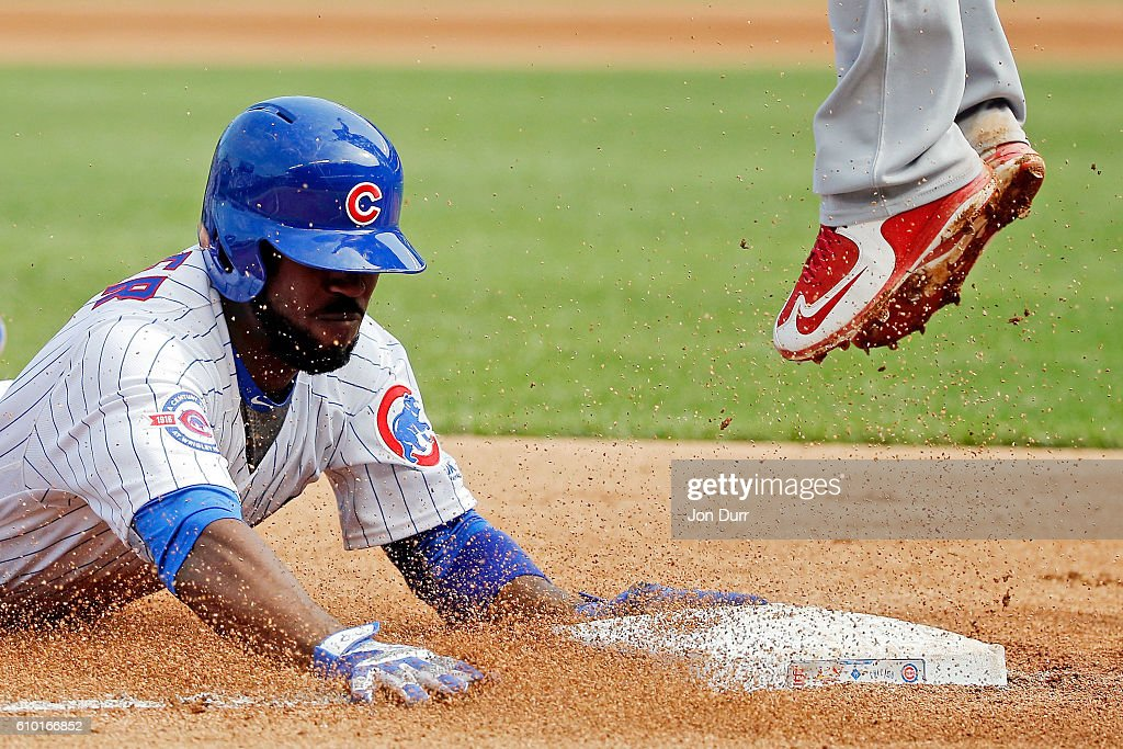 Dexter Fowler #24 of the Chicago Cubs safely dives into third base for a triple as Jhonny Peralta #27 of the St. Louis Cardinals jumps to make the catch during the fifth inning at Wrigley Field on September 24, 2016 in Chicago, Illinois.