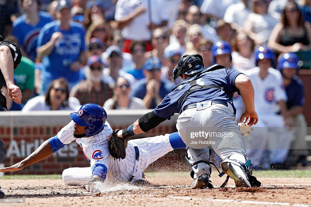 Dexter Fowler #24 of the Chicago Cubs slides at home plate ahead of the tag by Mike Zunino #3 of the Seattle Mariners in the seventh inning at Wrigley Field on July 30, 2016 in Chicago, Illinois. The Mariners defeated the Cubs 4-1.