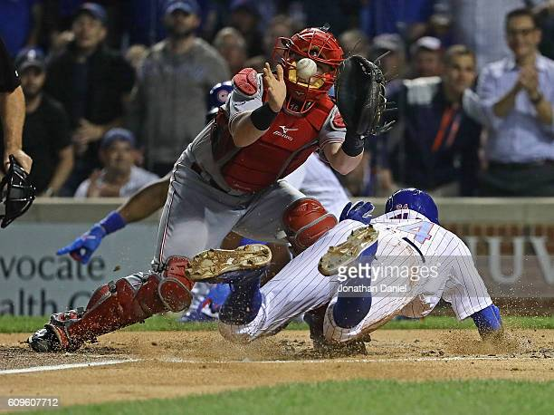 Dexter Fowler of the Chicago Cubs slides under Tucker Barnhart of the Cincinnati Reds to score a run in the 1st inning at Wrigley Field on September...