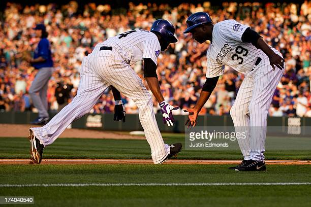 Dexter Fowler of the Colorado Rockies celebrates with third base coach Stu Cole after hitting a solo home run off of Jeff Samardzija of the Chicago...
