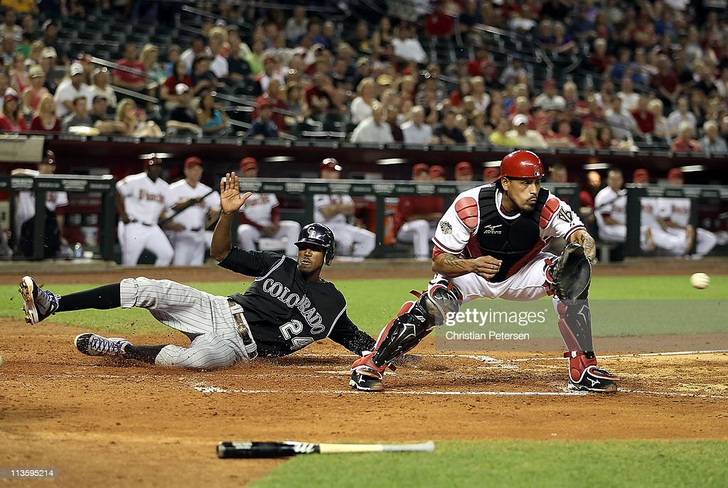 Dexter Fowler #24 of the Colorado Rockies safely slides in to score a run past catcher Henry Blanco #12 of the Arizona Diamondbacks during the fifth inning of the Major League Baseball game at Chase Field on May 3, 2011 in Phoenix, Arizona.