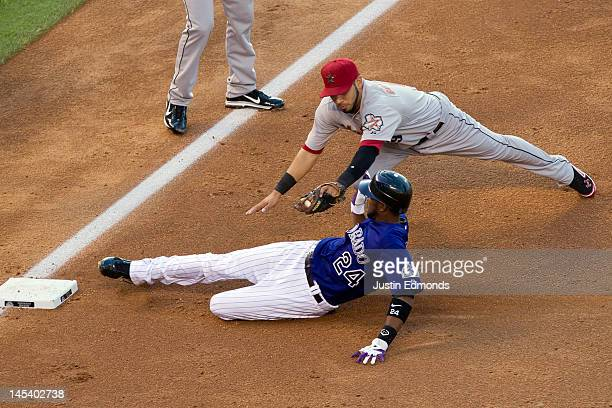 Dexter Fowler of the Colorado Rockies slides into third base safely ahead of the tag by Marwin Gonzalez of the Houston Astros after a bunt single and...