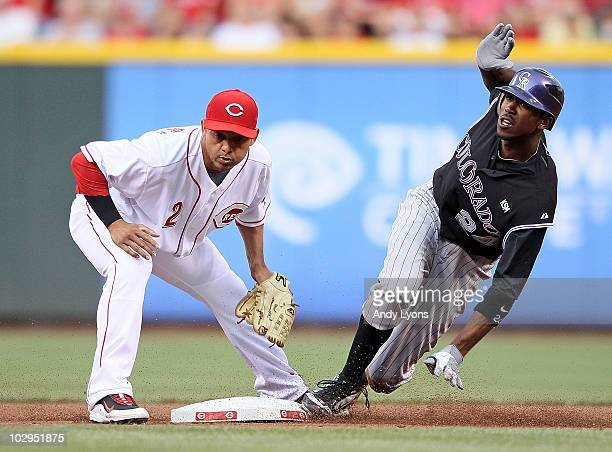 Dexter Fowler of the Colorado Rockies slides safely in front of the tag by Orlando Cabrera of the Cincinnati Reds during the game at Great American...
