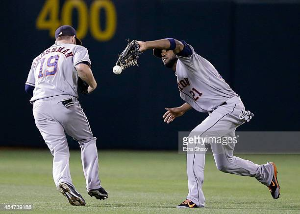 Dexter Fowler of the Houston Astros drops a ball hit by Coco Crisp of the Oakland Athletics as he almost collides with Robbie Grossman of the Houston...