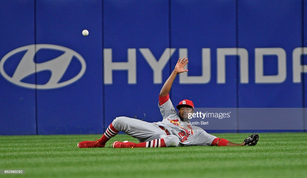 Dexter Fowler #25 of the St. Louis Cardinals cannot come up with a three run RBI triple off the bat of Jordy Mercer #10 of the Pittsburgh Pirates in the first inning during the game at PNC Park on September 23, 2017 in Pittsburgh, Pennsylvania.
