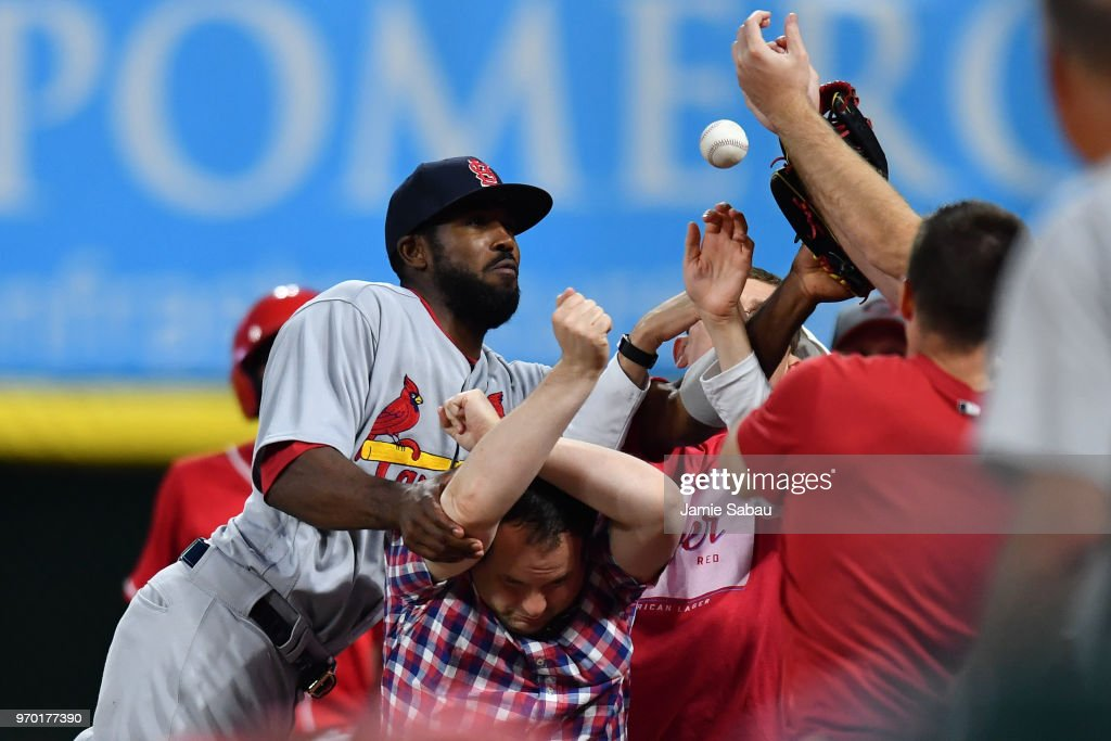 Dexter Fowler #25 of the St. Louis Cardinals collides with fans while chasing down a foul ball in the sixth inning against the Cincinnati Reds at Great American Ball Park on June 8, 2018 in Cincinnati, Ohio. Fowler dropped the ball.