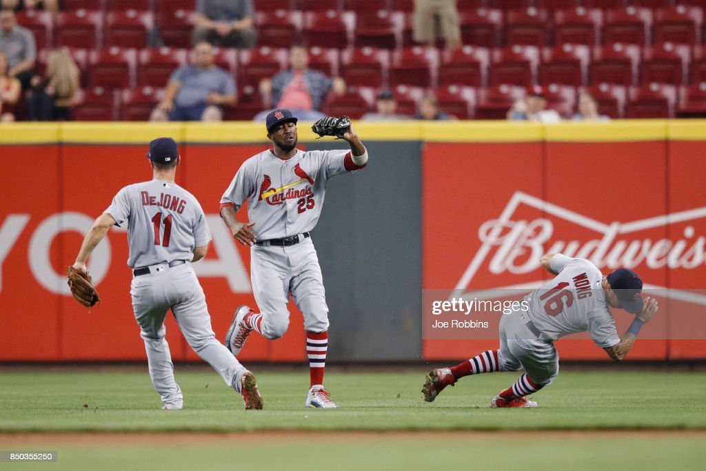 Dexter Fowler #25 of the St. Louis Cardinals makes a catch between Paul DeJong #11 and Kolten Wong #16 in the seventh inning of a game against the Cincinnati Reds at Great American Ball Park on September 20, 2017 in Cincinnati, Ohio. The Cardinals won 9-2.