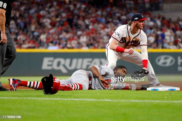 Dexter Fowler of the St Louis Cardinals slides in safely to third base as Josh Donaldson of the Atlanta Braves attempts to tag him out during the...