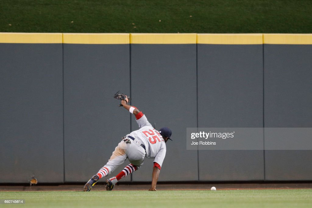 Dexter Fowler #25 of the St. Louis Cardinals tries to play a two-run double hit by Eugenio Suarez of the Cincinnati Reds in the seventh inning of a game at Great American Ball Park on June 5, 2017 in Cincinnati, Ohio. The Reds defeated the Cardinals 4-2.