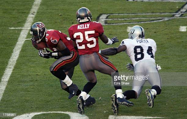 Dexter Jackson of the Tampa Bay Buccaneers intercepts a pass intended for Jerry Porter of the Oakland Raiders with the help of teammate Brian Kelly...