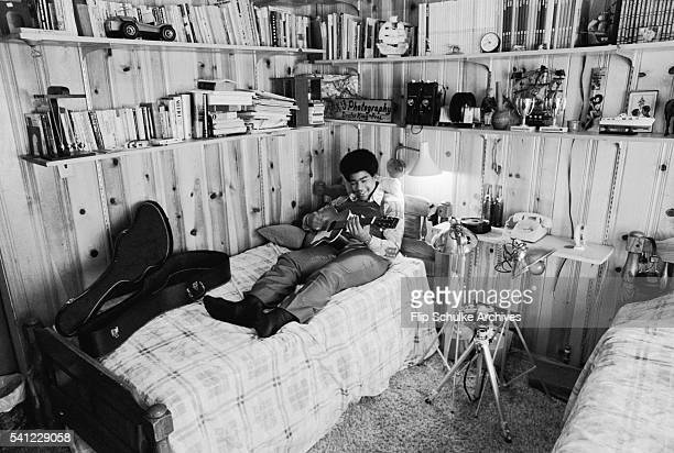 Dexter King son of Martin Luther King Jr plays a guitar while lounging in his bedroom