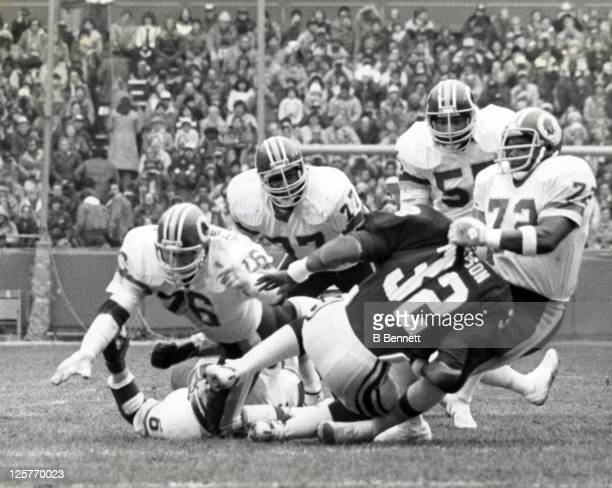 Dexter Manley of the Washington Redskins tackles Ottis Anderson of the St Louis Cardinals as Manley's teammates Mat Mendenhall Darryl Grant and Mel...
