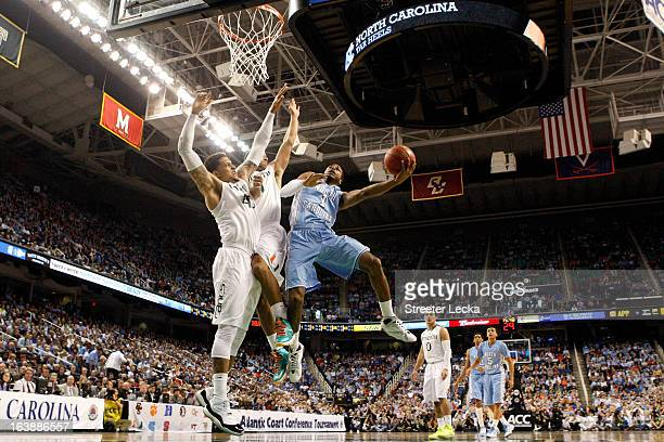 Dexter Strickland of the North Carolina Tar Heels drives for a shot attempt in the first half against Julian Gamble and Trey McKinney Jones of the...