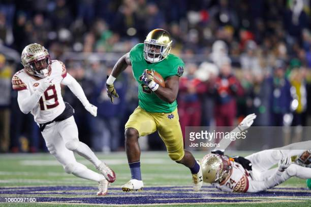 Dexter Williams of the Notre Dame Fighting Irish breaks a tackle on his way to a 58yard touchdown run against the Florida State Seminoles in the...