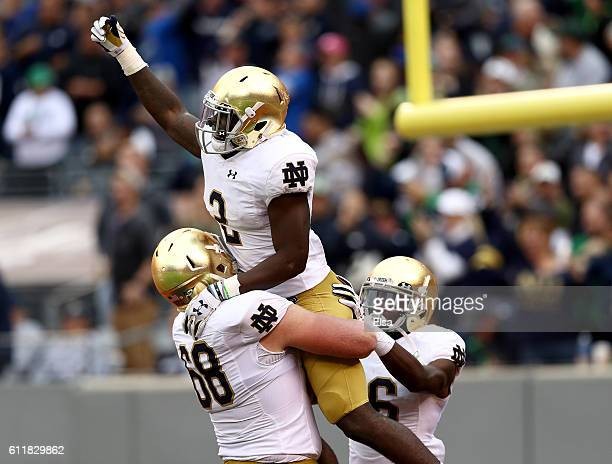 Dexter Williams of the Notre Dame Fighting Irish celebrates his touchdown with teammates Mike McGlinchey and Torii Hunter Jr #16 in the second half...