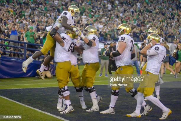 Dexter Williams of the Notre Dame Fighting Irish is lifted in celebration after scoring a touchdown in the 1st half against the Navy Midshipmen at...