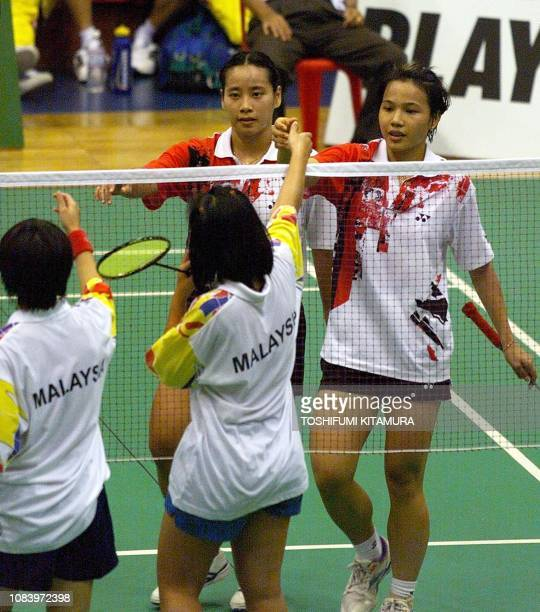 Deyana Lomban and Elysa Nathanael of Indonesia reach to shake hands with Malaysia's Lim PekSiah and Chor HooiYee after winning their doubles match in...