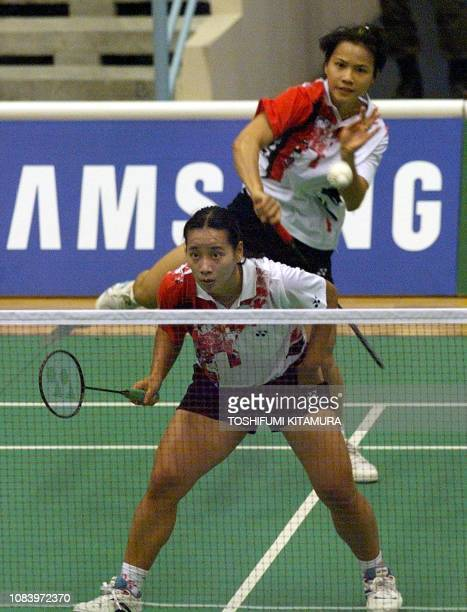 Deyana Lomban of Indonesia smashes a shuttle while her partner Elysa Nathanael takes position during their doubles match against Malaysia's Lim...