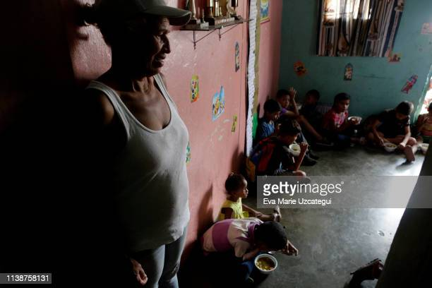 Deysa who offered her house at Barrio Union to feed 60 children looks at them while they eat soup prepared by Alto Restaurant in Petare on April 12...